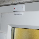 Wireless Magnetic Contact fitted onto a PVC Door.